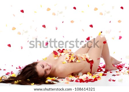 Semi naked beautiful brunette woman lying on bed of red yellow and orange rose petals isolated on a white background - stock photo