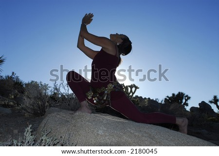 Semi silhouette of Woman in yoga pose outdoors in the desert.
