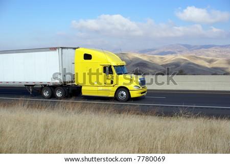 Semi-trailer rig heads west into the Sierra Nevada Mountains, California - stock photo