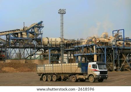 Semi-trailer truck in industrial sugar refinery plant - stock photo