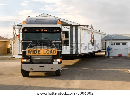 Semi-Truck backing in a mobile home. - stock photo