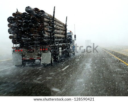 Semi truck driving down highway during blizzard snow storm - stock photo
