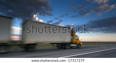 Semi-truck driving during sunset - stock photo