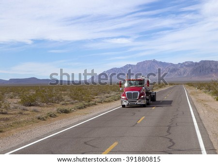 SEMI TRUCK DRIVING ON HIGHWAY, USA  - January 20, 2016: Semi truck going fast on the desert mountain highway  - stock photo