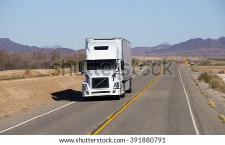 SEMI TRUCK DRIVING ON HIGHWAY, USA  -  MARCH 1, 2016: Semi truck going fast on the desert mountain highway