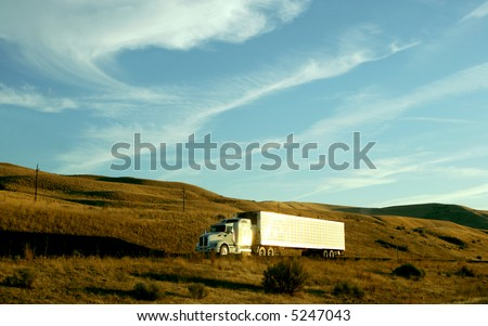 Semi truck going up hill on interstate highway at sunset - stock photo