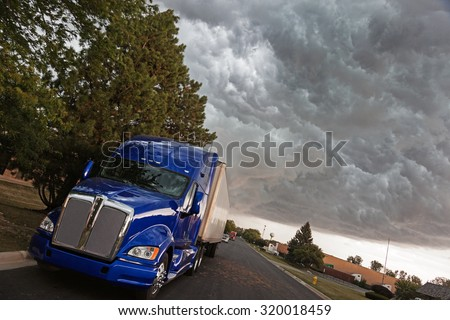Semi Truck in the industrial area under heavy clouds - stock photo