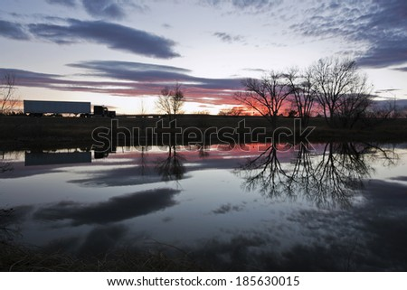 Semi Truck seen during sunset - reflected in the pond - stock photo