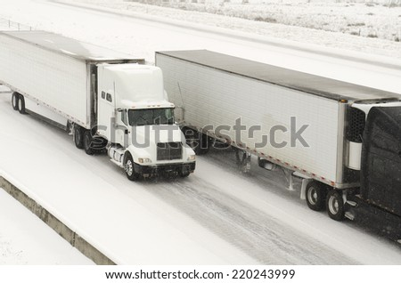Semi truck traffic on Interstate 5 during a winter snow and freezing rain storm - stock photo