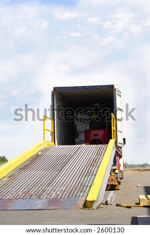 Semi truck with forklift driver in back of container - stock photo