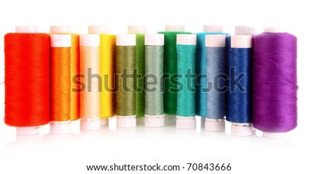 Semicircle of many-coloured bobbins of thread isolated on white