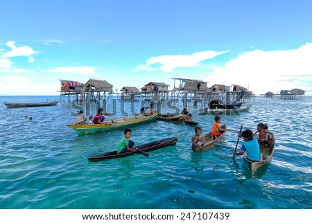 SEMPORNA, MALAYSIA - JULY 3 : Unidentified Sea Bajau's children play and rowing a boat on July 3, 2009 in Sabah, Malaysia. Children here do not attend school for lack of means and resources. - stock photo