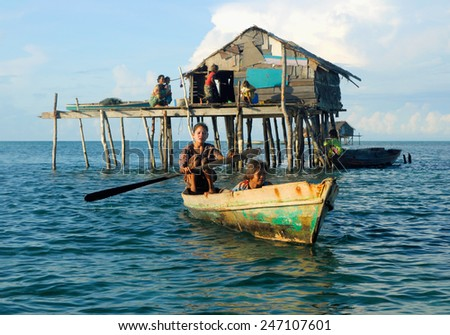 SEMPORNA, MALAYSIA - JULY 5 : Unidentified Sea Bajau's children rowing a boat July 5, 2009 in Sabah, Malaysia. The Sea Gypsies are sea nomads that move from one place to another. - stock photo