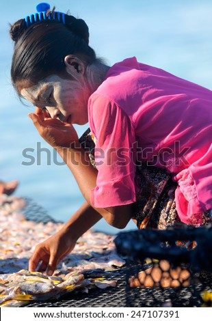 SEMPORNA, MALAYSIA - JULY 5 : Unidentified Sea Bajau's girl picking dry fish during sunny day on July 5, 2009 in Sabah, Malaysia. The Sea Gypsies are sea nomads that move from one place to another. - stock photo
