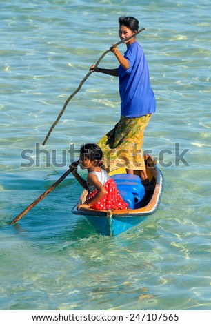 SEMPORNA, MALAYSIA - JULY 5 : Unidentified sea gypsies woman with kid paddle a boat on July 5, 2009 in Sabah, Malaysia. Children here do not attend school for lack of means and resources. - stock photo