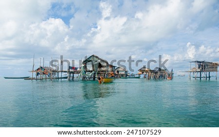 SEMPORNA, MALAYSIA - MAY 10 : Unidentified Sea Bajau's children rowing a boat on May 10, 2009 in Sabah, Malaysia. The Sea Gypsies are sea nomads that move from one place to another. - stock photo