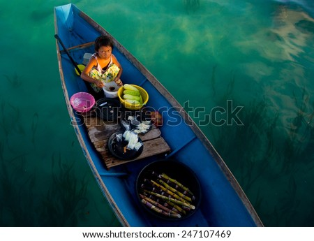 SEMPORNA, MALAYSIA - MAY 10 : Unidentified Sea Bajau's children selling fruits with boat on May 10, 2009 in Sabah, Malaysia. Children here do not attend school for lack of means and resources. - stock photo