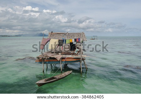 SEMPORNA, SABAH, MALAYSIA - OCT  2010 : Unidentified kids paddle a dug out boat  in Semporna, Sabah, Malaysia. They inhabit villages built on stilts in the middle of ocean.