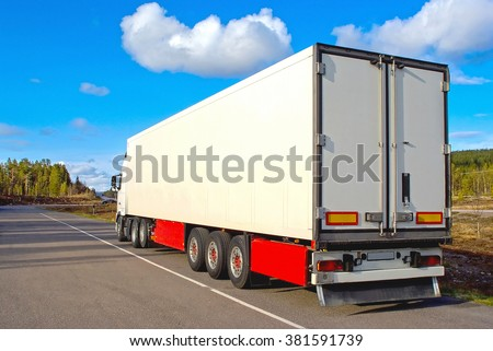 Semtrailer on the rural road in sunny day - stock photo