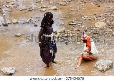 SENBETE, ETHIOPIA-MARCH 24, 2013: Women of the oromo people chat and wash their bodies in the water of the river flowing across the market on March 24, 2013. Senbete-Oromia zone-Amhara region-Ethiopia