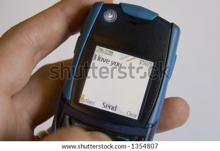 Sending a cellular phone SMS message to a loved one - stock photo