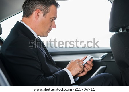 Sending an urgent message. Side view of confident mature businessman typing message on his smart phone while sitting on the back seat of a car  - stock photo