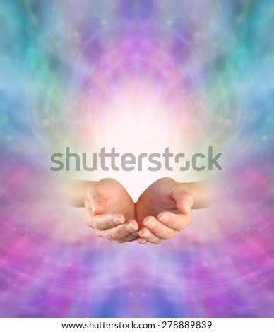 Sending Divine Healing Energy -  Female cupped hands on an ethereal pink and blue energy formation background with a burst of white light rising up and plenty of copy space - stock photo
