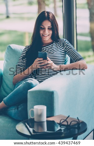 Sending message to him. Beautiful young smiling woman looking at her smart phone while sitting in a big comfortable chair at home