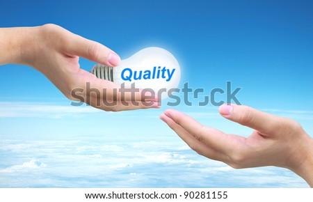 sending quality light bulb on women hand - stock photo