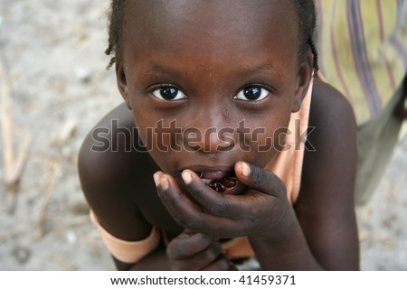 SENEGAL - FEBRUARY 18: Girl on the island of Carabane posing while carrying food to their mouths, February 18, 2007 in Carabane, Casamance, Senegal - stock photo