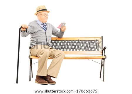 Senile old man with cane, sitting on bench imagining playing cards with someone else, isolated on white background - stock photo