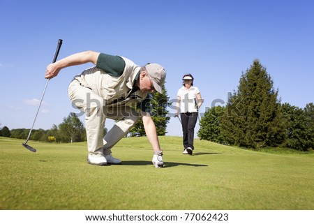 Senior active male golf player picking up golf ball from hole on green with female golf player walking in background with fantastic blue sky. - stock photo