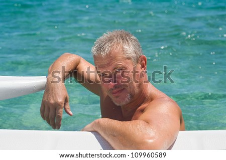Senior active man getting a workout at the swimming pool - stock photo