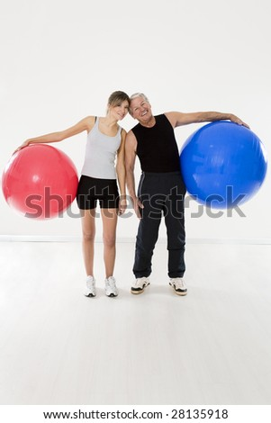 senior adult and daughter exercising with fitness ball in gym - stock photo