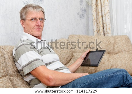 Senior adult Caucasian man working with a new tablet device, sitting on sofa in domestic room - stock photo