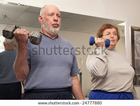 Senior Adult Couple Working Out in the Gym. - stock photo