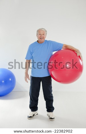 senior adult exercising with fitness ball in gym - stock photo