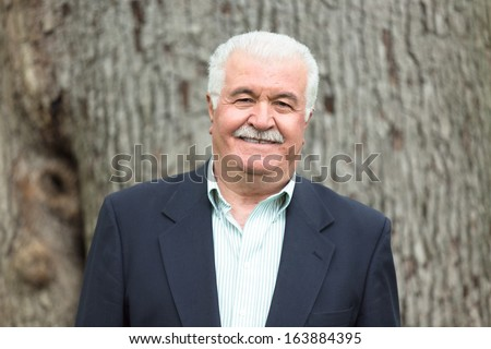Senior adult looking at you smiling and satisfactorily in-front of big tree trunk - stock photo