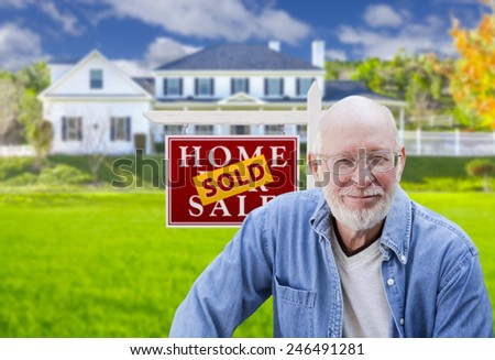 Senior Adult Man in Front of Sold Home For Sale Real Estate Sign and Beautiful House. - stock photo