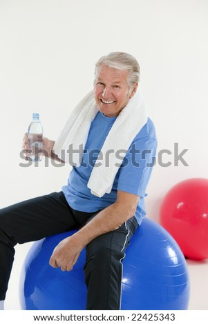 senior adult sitting on fitness ball in gym and holding water bottle - stock photo