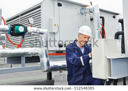 senior adult ventilation electrician builder engineer at work - stock photo