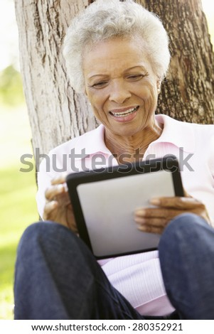 Senior African American Woman In Park Using Tablet Computer - stock photo