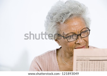 Senior African American woman reading newspaper - stock photo
