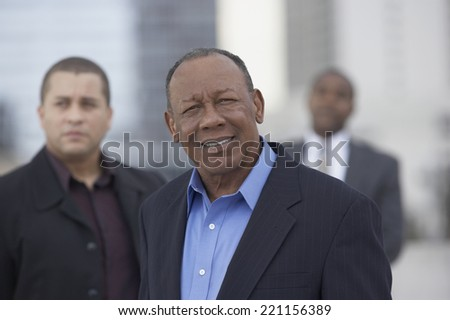 Senior African businessman with coworkers in background - stock photo