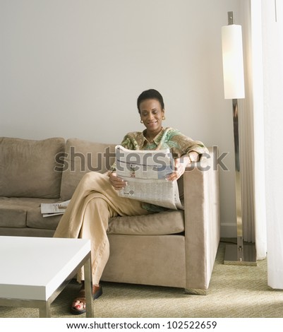 Senior African woman reading newspaper - stock photo