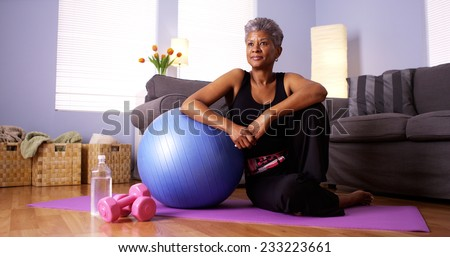 Senior African woman sitting on floor with exercise equipment - stock photo