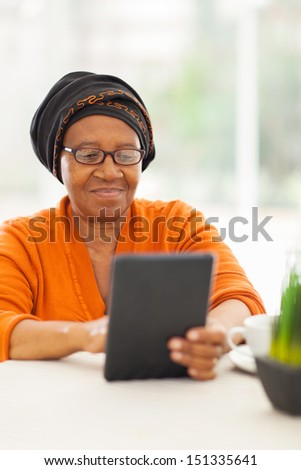 senior african woman using tablet computer at home - stock photo