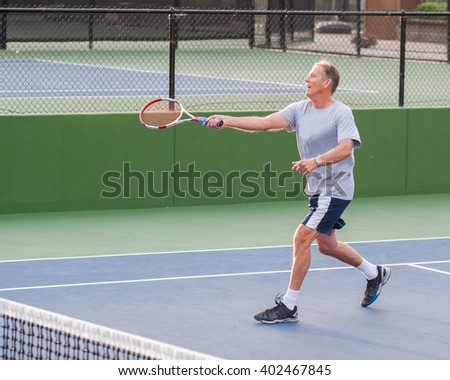 Senior age man showing perfect follow through on running volley. - stock photo