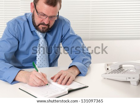senior aged business man working in his office - stock photo