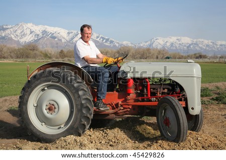 senior aged man driving on a small farm tractor